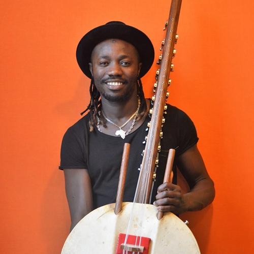 Ablaye Badji - zdjęcie artysty, trzymającego afrykański instrument: korę